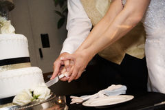 Cutting a wedding cake. A bride and groom holding a knife together, cutting a wedding cake Royalty Free Stock Photo