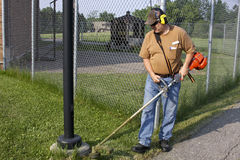 Cutting weeds. Landscape worker cutting weeds wearing hearing protection Stock Images