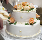Cutting a white wedding cake. Nice wedding cake with cream and flower decorations Stock Photos