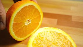 Cutting whole orange on a light wooden cutting board, close up video stock video