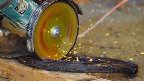 Cutting wire with circular saw in sparks shower on workbench