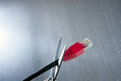 Cutting with wired technology, ethernet R. Cutting with wired technology metaphor, ethernet RJ45 cable scissors stock photography