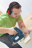 Cutting wood with electric saw Stock Image