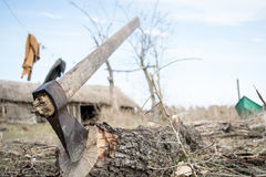 Cutting wood in a fisherman`s garden. Fisherman`s garden landscape of a boat and a sweater and an ax in the foreground and in focus royalty free stock photos