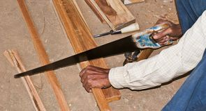 Cutting wood by hand saw Stock Photo
