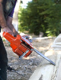 Cutting wood with motor saw. Man cutting wood with motor saw royalty free stock photography