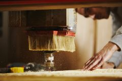 Cutting wood using a machine with numerical control. Cnc tool. Woodworking industry stock photography