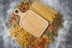 Cutting wooden board in the center with space for your text lies in the abundance of pasta.  Royalty Free Stock Image