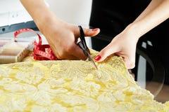 Cutting the yellow silk cloth Stock Photos