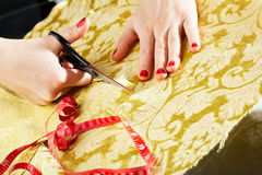 Cutting the yellow silk cloth Stock Images
