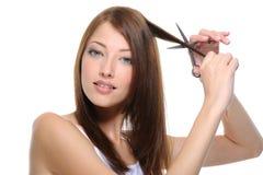 cuttinghår s scissors kvinnan Arkivfoto