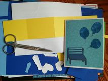 Cuttings, scissors and finished greeting card with balloons and bench. Measures for handicrafts: scissors,  rule and beautiful sheets of cartons Royalty Free Stock Images