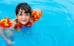 Cuttle little girl in swimming pool. A cute little girl with hazel eyes, wearing an inflatable life vest, having fun in swimming pool Royalty Free Stock Photo