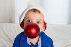 Cuttle little kid in Santa Claus hat playing with Christmas Bubb Stock Images