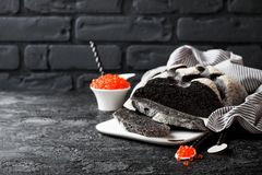 Cuttlefish ink bread and red caviar on black background Stock Photo