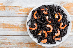 Cuttlefish ink pasta with prawns on white plate. Delicious Cuttlefish ink pasta with prawns on white dish on old wooden planks, horizontal view from above, close Stock Photography