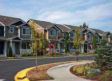 Cuved Row of Modern Townhouses. This curved street shows a row of modern American townhouse community in neutral colors for a beautiful neighborhood Royalty Free Stock Photo