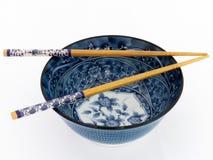 Cuvette asiatique bleue de porcelaine avec des baguettes Photographie stock libre de droits