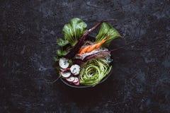 Cuvette asiatique crue avec les nouilles de riz, la carotte, le radis et le concombre sur le fond noir Vue supérieure photo libre de droits