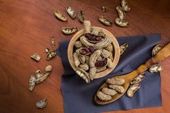 Cuvette avec des arachides avec la coquille et ?pluch?es avec une cuill?re sur une surface en bois photos stock