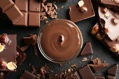 Cuvette avec du chocolat fondu et les barres coupées Images stock
