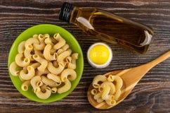 Cuvette avec le cavatappi cru de pâtes, huile végétale, macaronis dans la cuillère, dispositif trembleur de sel sur la table en b image libre de droits