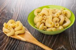 Cuvette avec le cavatappi de pâtes, cuillère en bambou avec des macaronis sur la table en bois photo libre de droits