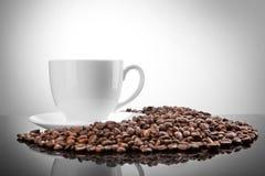 Cuvette blanche avec des grains de café sur le blanc Photographie stock libre de droits