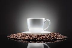 Cuvette blanche avec des grains de café sur le noir Images libres de droits