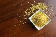 Cuvette blanche avec des grains de millet sec jaune sur une table en bois, vue supérieure photographie stock libre de droits