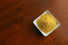 Cuvette blanche avec des grains de millet sec jaune sur une table en bois, vue supérieure photos stock