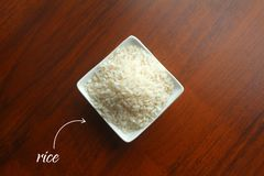 Cuvette blanche avec des grains du riz blanc sur une table en bois, vue supérieure image libre de droits