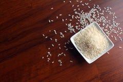 Cuvette blanche avec des grains du riz blanc sur une table en bois, vue supérieure Grains aléatoirement dispersés autour de la cu images libres de droits