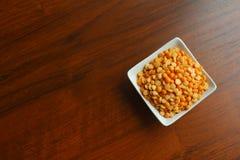 Cuvette blanche avec des grains des pois secs jaunes sur une table en bois, t photographie stock libre de droits