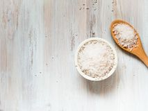 Cuvette blanche avec du grand sel de mer et la cuillère en bois sur la table en bois blanche photo libre de droits