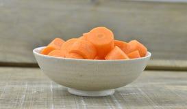 Cuvette blanche avec les carottes coupées profondément sur le fond en bois photo libre de droits