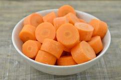 Cuvette blanche avec les carottes coupées profondément sur le fond en bois image libre de droits