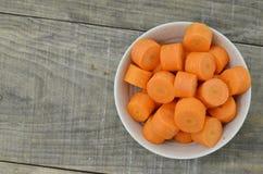 Cuvette blanche avec les carottes coupées profondément sur le fond en bois photo stock