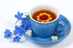 Cuvette bleue de thé avec des fleurs Images stock