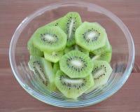 Cuvette complètement avec la haute dans des tranches de kiwi de vitamines sur le fond en bois Images libres de droits