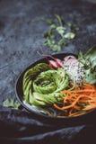 Cuvette crue de vegan avec la carotte, le concombre, le radis et l'avocat sur le fond noir Fermez-vous vers le haut avec l'espace image libre de droits