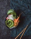 Cuvette crue de vegan avec les nouilles de riz, la carotte, le radis et l'avocat sur le fond noir Vue supérieure images stock