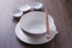 Cuvette, cuillère, bol de sauce et baguettes blancs sur la table en bois Photos libres de droits