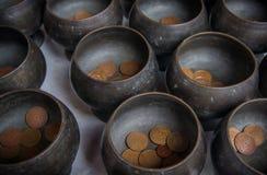 Cuvette d'aumône de Monk's et pièce de monnaie thaïlandaise données photos libres de droits