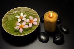 Cuvette de bougie et de fleurs et pierre noire Image libre de droits