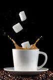Cuvette de café avec éclabousser des cubes en sucre photographie stock