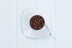 Cuvette de café avec des grains de café sur la table Image libre de droits