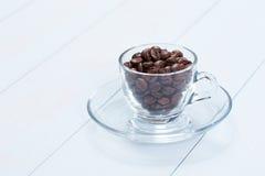 Cuvette de café avec des grains de café sur la table Images stock