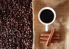 Cuvette de café avec des haricots et des bâtons de cannelle Photo stock