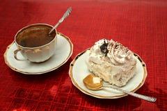 Cuvette de café avec la cuillère et une part de secteur sur le backgroun rouge Photos stock